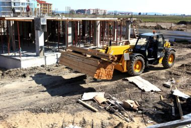 Heavy Machinery Loading Wood In Construction Site