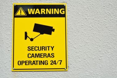 """Yellow sign with """"Security Cameras in Operating 24/7"""""""